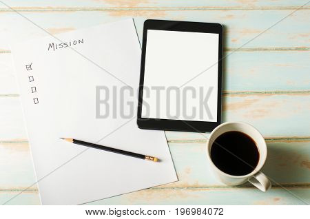 Digital tablet on skyblue color desk with blank white screen. Check list on paper for planning work. Check list Sheet for mission.