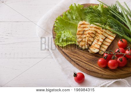 Grilled slices of homemade halloumi cheese with green salad fresh herbs and organic tomatoes. Fried halloumi cheese with grill marks on white wooden background top view