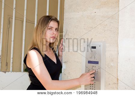 Woman Blond Dialing Intercom In City Center