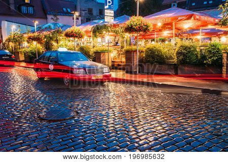 Riga, Latvia - July 3, 2016: Taxi Car Mercedes-Benz W140 Wait Clients Near Open Air Leisure Venue Recreation Center Egle In Evening Or Night Illumination In Old Town On Kalku Street