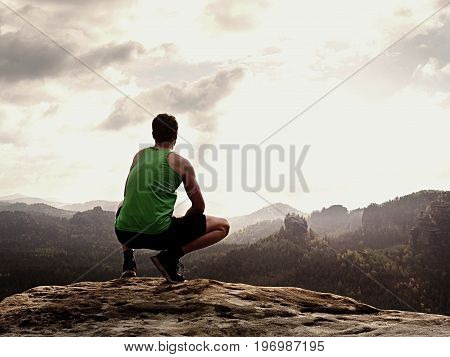 Adult Hiker In Black Shorts And Green Singlet Sit On Mountain  Edge. Man Enjoying View
