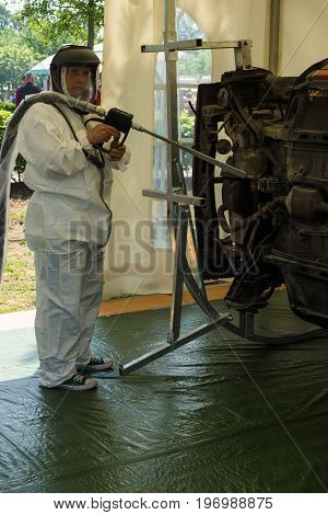 PAAREN IM GLIEN GERMANY - MAY 23 2015: Repairman demonstrates the device for cleaning the car body against corrosion. The oldtimer show in MAFZ.