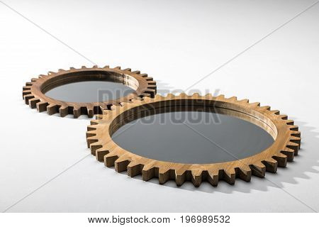 Close-up View Of Mirrors Framed By Wooden Cogwheels Lying On White