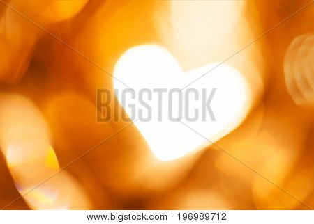 Glowing golden blurred background with heart. Concept of love