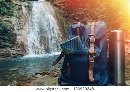 Hipster Blue Backpack Map And Thermos Closeup. View Front Tourist Traveler Bag On Waterfall Background. Adventure Hiking Concept