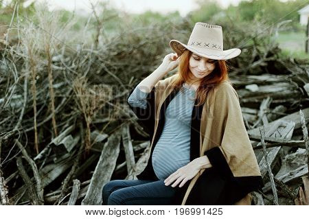 A pregnant woman expecting a baby in cowboy wear at sunset. Expecting Cowgirl. Pregnancy. A photo of a cute caucasian pregnant