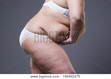Overweight woman with fat abdomen obesity female body on gray background