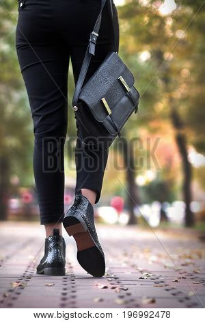 A girl steps in python leather shoes. Autumn fashion for a girl