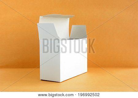 Open white cardboard box on light brown background - soft focus