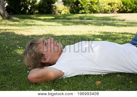 Handsome Teenager Boy Lies On Grass And Thinks
