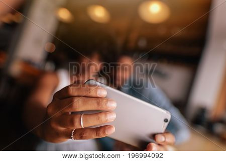 Close up of female hands holding smart phone and taking selfie. Young woman taking selfie with mobile phone while sitting at cafe with her boyfriend. Couple taking self portrait with smart phone. Focus on mobile phone in woman's hands.