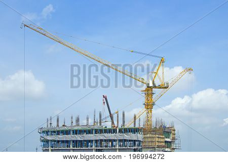 Crane lifts building with construction workers on daylight