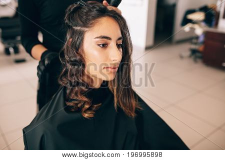 Close up of young woman at the salon getting her hair styled. Hair stylist turning straight hair into curly.