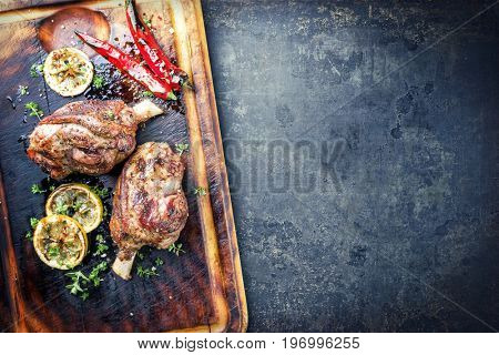 Barbecue Leg of Lamb with Tomato Chili Relish as top view on burnt cutting board