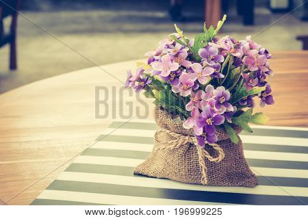 Purple flowers in small jute bag on the table - vintage (retro) style color effect