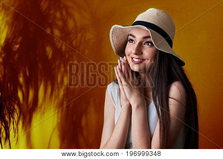 Portrait Of Surprised A Smiling Pretty Girl In Summer Hat Posing Isolated Over Yellow Tropic Backgro