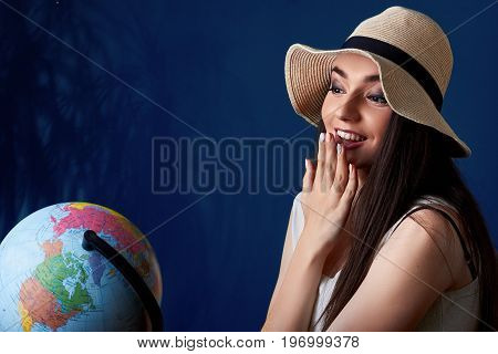 Portrait Of Surprised A Smiling Pretty Girl With Globe In Hands In Summer Hat Posing Isolated Over B