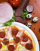Pizza with salami, ham, edd and tomato, on a table poster