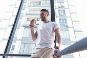 City lifestyle. Low angle of satisfied bearded man in casual clothes is standing on staircase with coffee. He is expressing gratification while drinking beverage poster