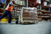 Blurred motion shot of warehouse worker wearing hardhat and reflective jacket pushing moving cart with boxes along isle between tall racks poster