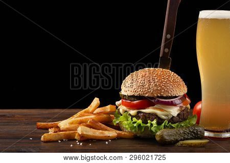 Homemade Hamburger With French Fries And Glass Of Beer On Wooden Table. In The Burger Stuck A Knife.