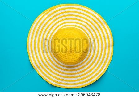 Top View Of Yellow Hat Close-up Over Blue Background. Minimalist Photo Of Striped Retro Hat Summer C