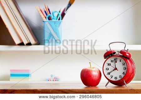 Alarm clock and apple on wooden table. Back to school conceptual image.
