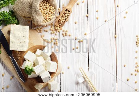 Soy Bean Curd Tofu In Wooden Bowl And In Hemp Sack On White Wooden Kitchen Table. Non-dairy Alternat
