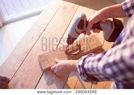 Hand with cordless drill fixing handle to a front of drawer, diy renovation of a vintage table series. Hobby concept