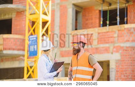 Discuss Progress Project. Safety Inspector Concept. Woman Inspector And Bearded Brutal Builder Discu