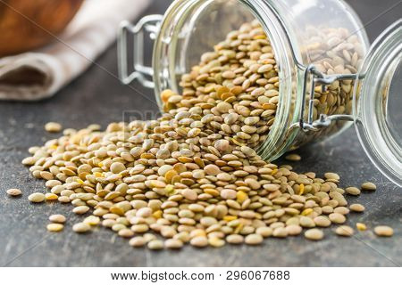 Uncooked dried lentil in jar.