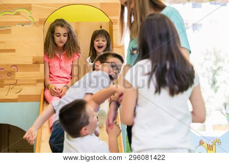 Cute pre-school girls smiling while sitting on a wooden slide during playtime supervised by a young teacher in the classroom of a modern kindergarten