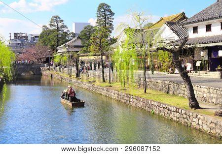 People in old-fashioned boat, Kurashiki canal in Bikan district, Kurashiki city, Japan