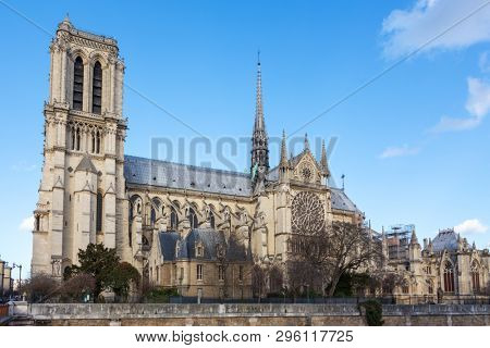 Notre Dame Cathedral in Paris. Springtime view of the side elevation with spire and rear flying buttresses, taken from across the river Seine.