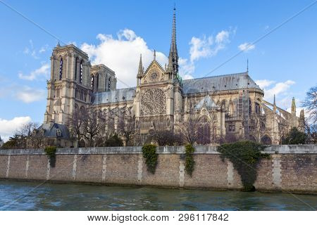 Notre Dame Cathedral in Paris. Springtime view. of the side elevation with spire and rear flying butresses, taken from across the river Seine.