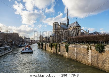 Notre Dame Cathedral in Paris. Springtime view of the rear elevation with spire and rear flying buttresses, taken from across the river Seine. People not recognisable when viewed at 100%