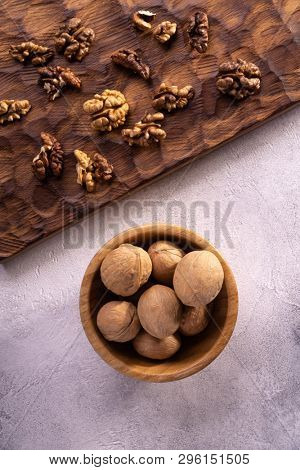 Walnuts in wooden bowl and on wooden carved board on bright textured surface, top view. Healthy nuts and seeds composition.