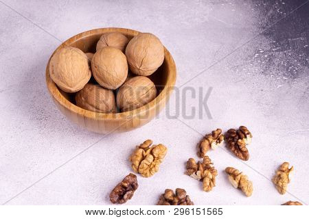 Walnuts in wooden bowl on bright textured surface, side view. Healthy nuts and seeds composition.