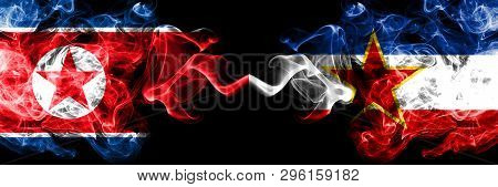 North Korea Vs Yugoslavia Smoky Mystic Flags Placed Side By Side. Thick Colored Silky Smoke Flags Of