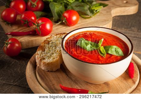 Fresh, Healthy Tomato Soup With Basil, Pepper, Garlic, Tomatoes And Bread On Wooden Background. Span