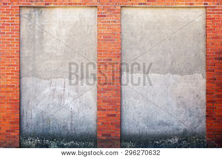 Weathered Stucco Wall And Red Brick Frame Around.