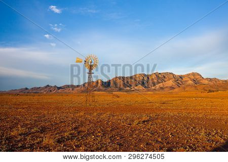 A Windmill With The Flinders Ranges Behind It In The Australian Outback. Flinders Ranges National Pa