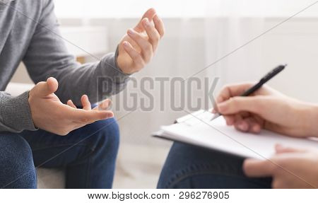Psychotherapist Writing Notes, Assessing Patients Health And Giving Diagnosis To Man Sitting On Couc