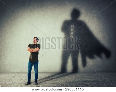 Casual Man, Keeps Arms Crossed Smiling Confident, Casting A Superhero With Cape Shadow On The Wall.