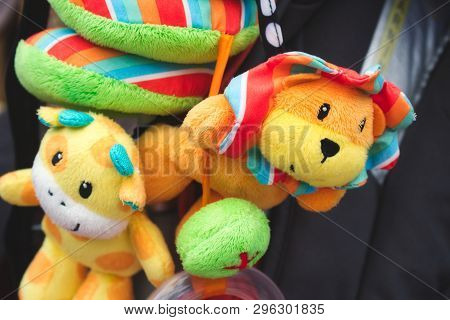 Soft Cuddly Toys Hanging From A Baby's Pushchair