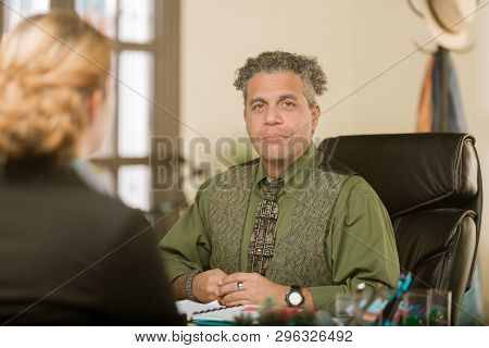 Creative Man At His Desk With Client Or Colleague