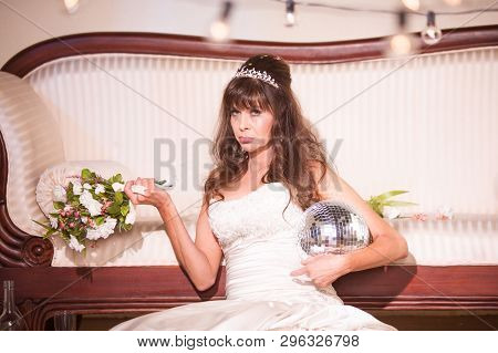 Unhappy Bride With A Disco Ball Sitting On The Floor