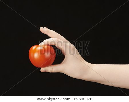 Childs hand with tomato