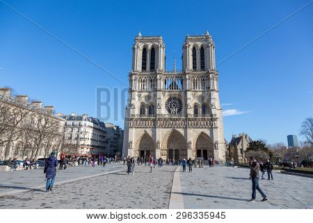 Paris, France - 2nd March 2015: Tourist in the square outside the Notre Dame Cathedral in Paris France. This is the famous two tower gothic front facade.