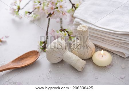 Spa setting with cherry flower with salt ,   spoon,candle, herbal ball ,towel, candle on gray ackground